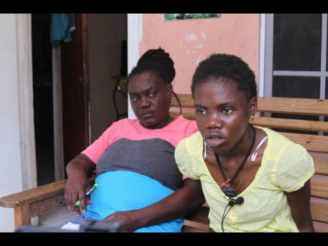 Shirley McIntosh looks on as her daughter, Nzinga King, talks to journalists about her ordeal at the Four Paths Police Station. The teenager alleges that a policewoman forcibly cut her hair.