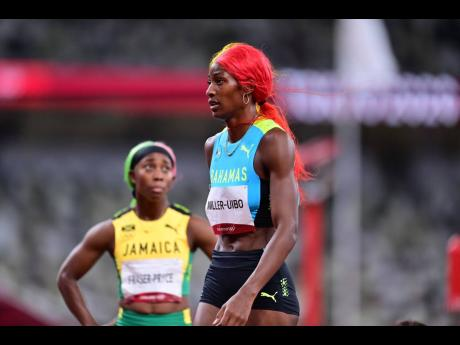 Jamaican sprinter Shelly-Ann Fraser-Pryce (left) looks for confirmation of her placing as The Bahamas' Shaunae Miller-Uibo walks by following the women's 200 metres final at the Tokyo 2020 Olympics, inside the Tokyo Olympic Stadium, Tokyo, Japan, yeste
