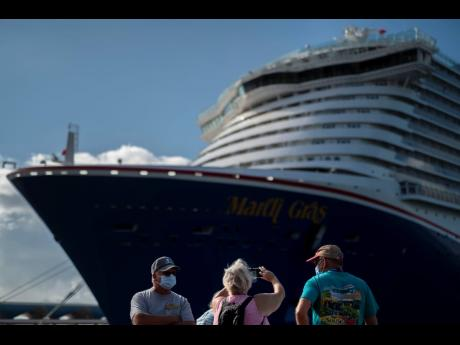 Tourists take pictures after exiting Carnival's Mardi Gras cruise ship, docked in the bay of San Juan, Puerto Rico, Tuesday, August 3, 2021.