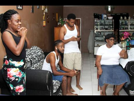 Paulette Goule-Garcia (right), mother of Natoya Goule, is joined by (from left) Ophelia Knight, Rakeem Knight and Orette Garcia to view the 2020 Tokyo Olympic Games women's 800 metres final at their home in Ebony Grove, Clarendon, yesterday. Natoya Goule
