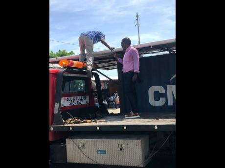 Craig Oates (right), enforcement and compliance officer at the Hanover Municipal Corporation, and a flatbed truck operator loading the seized items belonging to illegal vendors onto the truck.