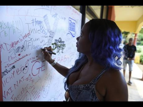 Simone Heath leaves her signature on the 'Dream Board' at the redemption centre for Dream Weekend 2018. Touted as the Caribbean's largest party festival, and Dream Weekend 2021 kicks off today.