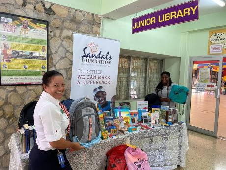 Regional Public Relations Manager at Sandals Grande Ocho Rios, Lyndsay Isaacs, spearheaded the donation of school supplies to the St Ann Parish Library on behalf of the Sandals Foundation. Isaacs (left) is pictured with senior librarian Opal Scott. The don