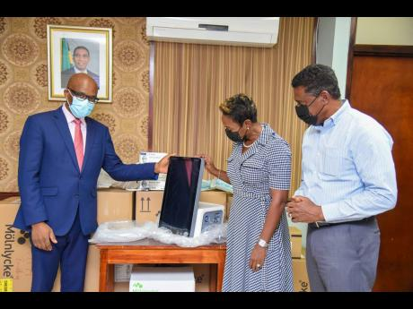 Minister of State in the Ministry of Health and Wellness, Juliet Cuthbert-Flynn (centre), looks at one of 23 ventilators that were donated by the government of the Kingdom of Saudi Arabia, along with other medical supplies,  to Jamaica to assist in combati