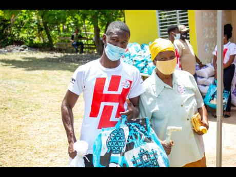 Jermaine Griffiths (left), technical sales associate at H&L Agro in Kingston, who took time off work to volunteer for H&L Giving Day, assists Ettis Thomas. More than 150 families received Food For The Poor care packages. H&L has announced that it has exten