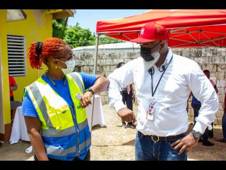 From left: Kivette Silvera, executive, Food For The Poor, and H&L CEO Marcus Richard,s managing director, H&L, at the recent H&L Giving Day, which took place at the Church of God of Prophecy in Botany Bay, St Thomas. More than  150 families received care p