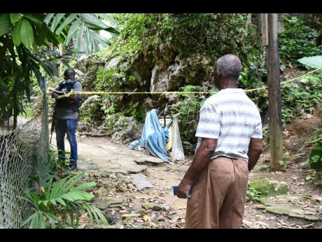 Lloyd Brown, grandfather of a victim in a triple murder, looks on as a policeman cordons off a dirt road leading to the house where the attack took place on Wednesday.