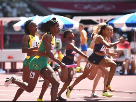 Shericka Jackson (foreground) collects the baton from Remona Burchell to snatch third place and a spot in the final of the 4x100m at the Tokyo Olympic Stadium.