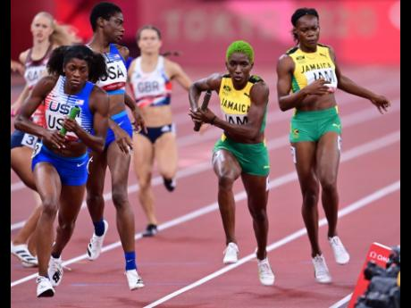 The USA's Kendall Ellis (left) receives the baton from Wadeline Jonathas (second left), ahead of Jamaica's Roneisha McGregor (right), who hands off to teammate Janieve Russell during the semi-final of the Women's 4x400m relay at the Olympic Games in Tokyo,