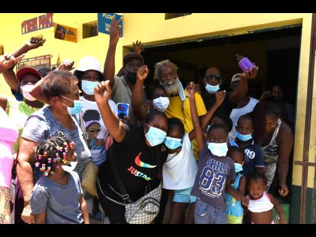 Residents of Seaside, St Thomas, throng Hensle Parchment, the Rastafarian dad of gold-medal hurdler Hansle Parchment, on Thursday.