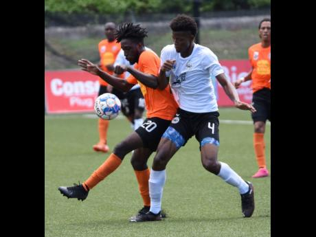 Tivoli Gardens FC's Anthony Nelson (left) is challenged for the ball by Richard King (right) from Cavalier during their Jamaica Premier League football match at the UWI/Captain Horace Burrell Centre of Excellence last Sunday.
