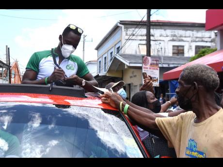 Hansle Parchment signs autographs during a stop on his motorcade yesterday.