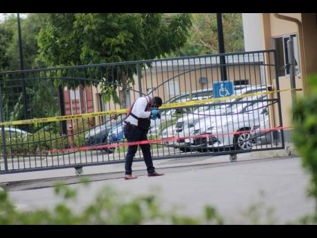 A policeman processes the scene where Granville gangster Oryon 'Chef' Williams was shot dead in the visitors' parking lot of Vista Print in Montego Bay, St James, yesterday.