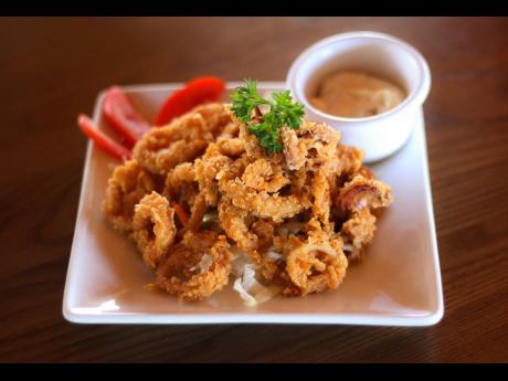 For patrons who indulge in seafood, a serving of fried calamari, battered to perfection, enhances the sensory quality and is sure to kick-start appetites.