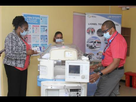Dr Rodger Hunter (right), president Medical Strategies Associates Ltd, and consultant neurosurgeon and spinal surgeon explains the features of the incubator to Nadine Preddie, chief executive officer, Lionel Town Hospital and  Vasantie Dubrey, specialist n
