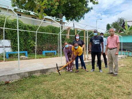 Main sponsor and vice-president of the Jamaica Association of Switzerland, Donna Hill (left, foreground), and representative of Moorland Development, Ashley Maxwell (right, foreground), break ground for the construction of a night shelter at Candle in the