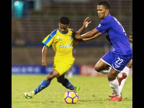 In the match-up of champions, Scott McLeod (right) of Kingston College defends against Clarendon College's Lamar Walker during the Olivier Shield schoolboy football showdown at the National Stadium in Kingston on Saturday, December 8, 2018. Plans are in