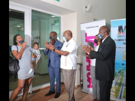 From left: Daynel Williams is excited on arrival as she and her baby, Keon Francis, are greeted by Shane Munroe, CEO of MBJ Airports Limited; Edmund Bartlett, minister of tourism; Kerry Ann Quallo-Casserly, regional commercial director, Royalton Blue Diamo