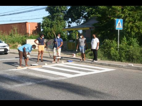 President of the Hanover Parish Development Committee, Petra Foster (right), along with volunteers painting the pedestrian crossing in the vicinity of the Sandy Bay Basic School in Hanover.