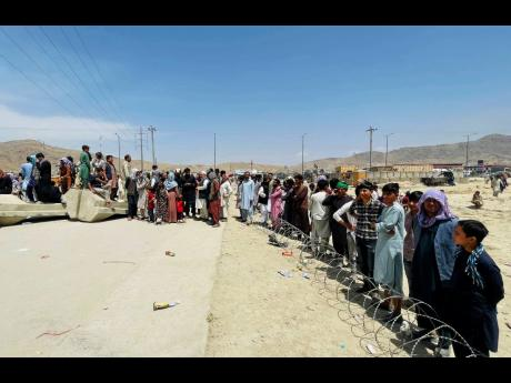 """Hundreds of people gathered outside the international airport in Kabul, Afghanistan last week. The Taliban declared an """"amnesty"""" across Afghanistan and urged women to join their government Tuesday, seeking to convince a wary population that they have c"""