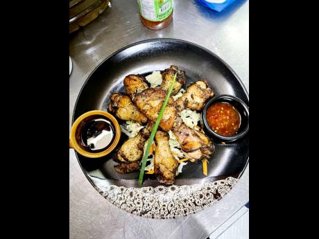 Signature jerk wings placed on a bed of steamed vegetables is served with a choice of two sauces. Dare to live on the spicy side of life.