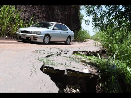 A motorist travels on Wednesday along the recently constructed Savage Pen road, sections of which have begun to collapse after torrential rain generated by Tropical Storm Grace slammed eastern parishes a day earlier. Savage Pen is the alternative route to
