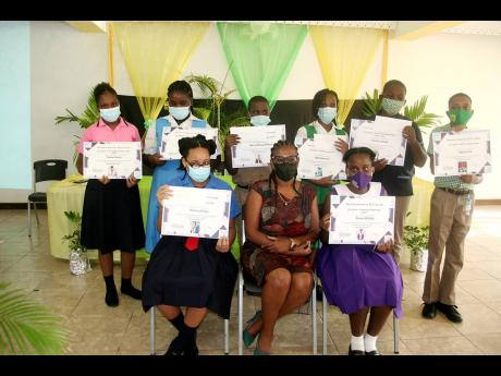 Member of Parliament for Hanover Western, Tamika Davis (seated centre), along with eight of the twenty top performing students from her constituency in the 2021 Primary Exit Profile examinations, pose for the camera following a two-part award ceremony held