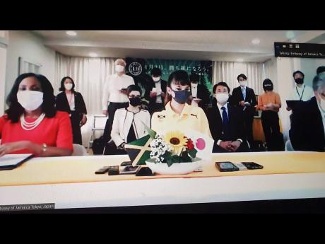Tijana Kawashima (right) and Jamaica's ambassador to Japan, Shorna-Kay Richards (left), are watched by Japanese dignitaries and media during an official ceremony announcing an invitation for Kawashima to visit Jamaica.
