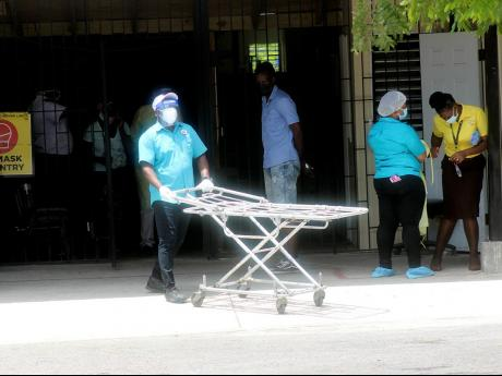 A porter pushes a gurney from the COVID-19 unit at the Cornwall Regional Hospital on Wednesday. Cornwall Regional and other hospitals were affected by an islandwide sickout.