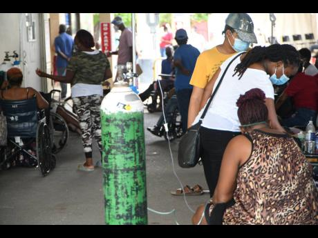 Patients on oxygen sitting in the driveway of the undercarriage at the Univerity Hospital of the West Indies waiting for assistance on Monday.