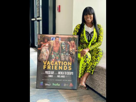 Press Kay poses with a plaque for 'Vacation Friends' from Hulu.