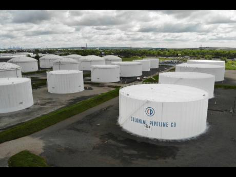 Colonial Pipeline storage tanks are seen in Woodbridge, N.J., Monday, May 10, 2021. Gasoline futures are ticking higher following a cyberextortion attempt on the Colonial Pipeline, a vital US pipeline that carries fuel from the Gulf Coast to the Northeast