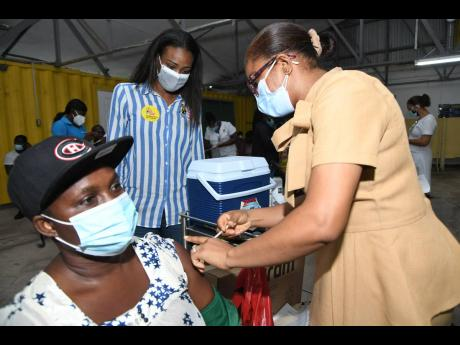 Nurse Nickesha Fowler Holdham (right) administers the COVID-19 vaccine to Lisa Grant while Ava Sinclair (centre), regional marketing manager at Best Dressed Chicken, looks on.