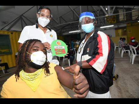 Nurse Tashia Allwood Carr (right) administers the COVID-19 vaccine to Oraine Manning, while Danah Cameron, (centre standing), group public relations manager at Best Dressed Chicken, looks on.