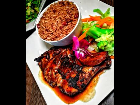 Drum pan jerk chicken served with rice and peas and steamed vegetables.