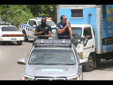 Health and Wellness Minister Dr Christopher Tufton (right) making an appeal to the people in Hopewell, Hanover, to get vaccinated against the coronavirus at the nearby Methodist Church Hall yesterday.