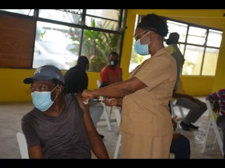 Nurse Merdella Brown-Madurie vaccinates Delroy Wisdom, AC technician at Tropical Tours, on Wednesday.
