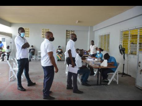 Bus drivers from Tropical Tours and Jamaica Tours wait their turn as they register for vaccinate at a blitz site on Wednesday.