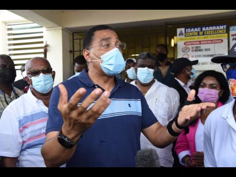 Prime Minister Andrew Holness addressing members of the media during a tour of the Isaac Barrant Health Centre in Hampton Court, St Thomas, on Wednesday.