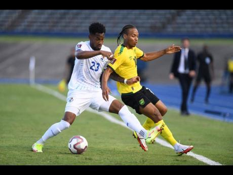 Jamaica's Bobby Reid (right) is bundled off the ball by Panama's Michael Murillo during their FIFA World Cup qualifying match at the National Stadium on Sunday afternoon.
