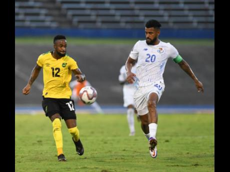 Jamaica's Junior Flemmings (left) plays the ball away while under pressure from Panama's Anibal Goday Lemus during Sunday night's Concacaf World Cup qualification match at the National Stadium. Panama won 3-0.