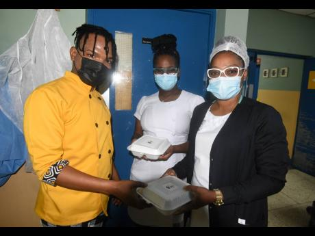 Andre Stephens, co-owner of Premier Kitchen, delivers food to nurses at the Kingston Public Hospital on Tuesday. He has committed to delivering 100 meals to frontline workers and homeless people for the next 21 days.