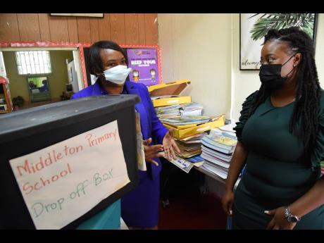 Middleton Primary School Principal Jennifer Crawford (left) and teacher Castorai Newell discuss where in the communities to places boxes to drop off and pick up assignments for students of the St Thomas-based school.