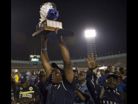Jamaica College team manager Ian Forbes lifts the ISSA/Digicel Manning Cup trophy after the school's victory in the final against St Andrew Technical High School at the National Stadium in Kingston on Friday December 1, 2017.