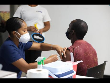 A Wisynco employee (right) receives his COVID-19 vaccination on Tuesday at the company's Lakes Pen headquarters in St Catherine. With logistical assistance from the PSOJ's Private Sector Vaccine Initiative, Wisynco underwrote the costs for the vaccinat