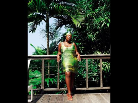 The birthday girl Mecca James-Williams donning her silk dress collaboration with SVNR that's dipped in green, yellow and black dyes as an ode to Jamaica.
