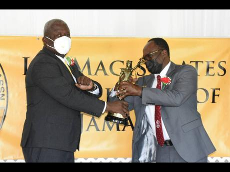 Dr Lynden Rose (right), president of the Lay-Magistrate Association of Jamaica presents one of the three Golden Scale awards to Rev Florizel Allen during the 25th Annual Golden Scale Awards at the Caymanas Golf Club on August 28.