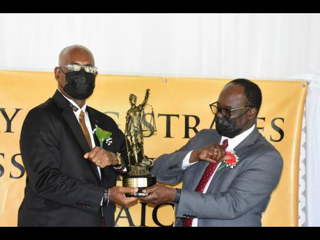 Howard Deers (left) JP from St James, accepts one of three Golden Scale Award from Dr Lynden Rose, presidednt of the Lay Magistrates Association of Jamaica.