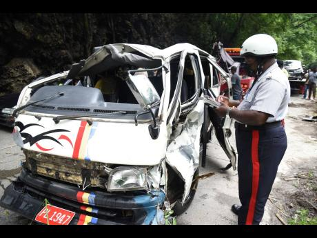 Police corporal Everton Allen jots down notes while observing the mangled Toyota Hiace minibus that had plunged into the Rio Cobre after colliding with a Toyota Fielder station wagon on Tuesday. Valerie Ennis, 59, died from crash-related injuries.