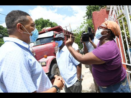 Linette Brown (right), a resident of Grants Pen, calls on Prime Minister Andrew Holness for national prayer during his Vaccine Mobilisation and Public Education Campaign tour in North East St Andrew and Central Kingston, while Desmond McKenzie (centre), m